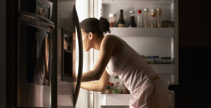 Young woman looking in refrigerator, night, side view